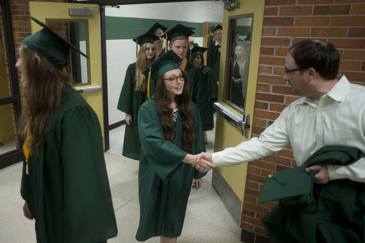H.H. Dow High graduating senior Danielle Rapanos, left, shakes hands with English teacher Andrew Frye before walking into the gym for the commencement ceremony Friday evening.