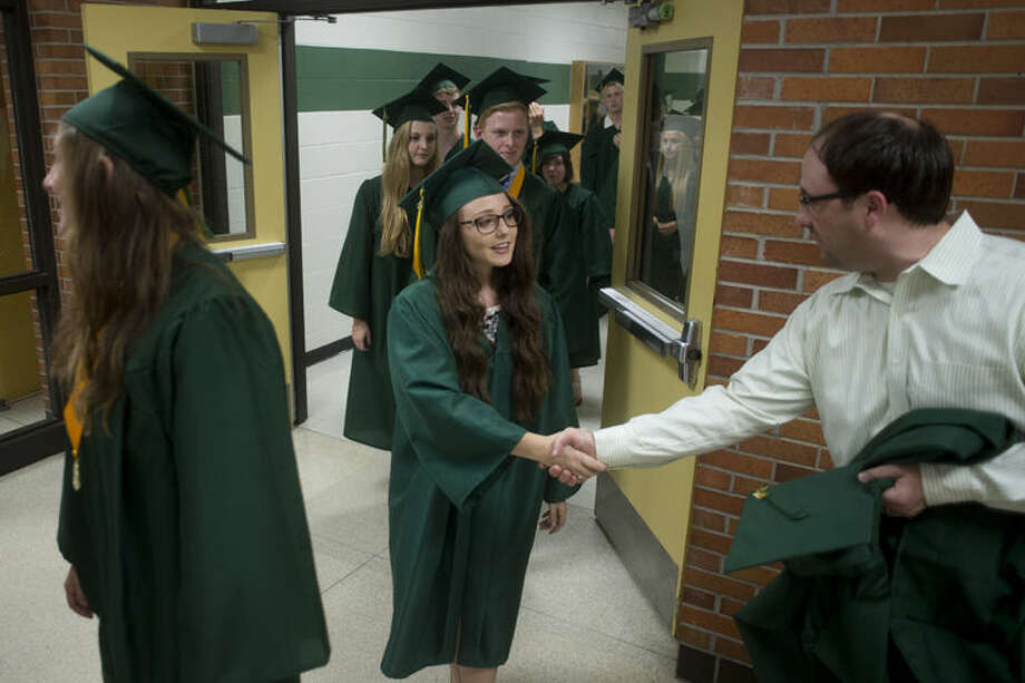 H.H. Dow High graduating senior Danielle Rapanos, left, shakes hands with English teacher Andrew Frye before walking into the gym for the commencement ceremony Friday evening. Photo: Brittney Lohmiller