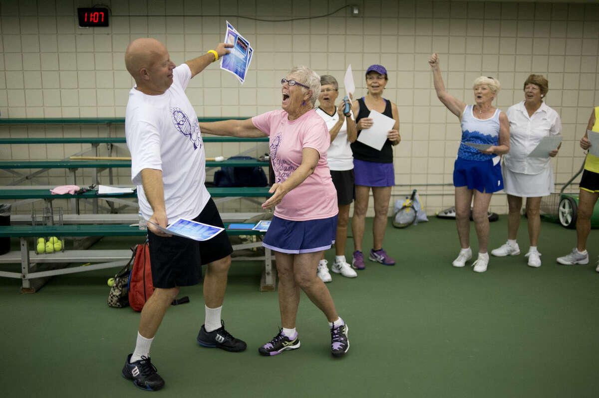 """NEIL BLAKE   nblake@mdn.net Greater Midland Tennis Center Executive Director Mike Woody hugs his mother, Carol Gassell of Howell, as he presents her with her certificate for completing the Gram Slam Camp for women 55 and older on Friday. """"We aren't good,"""" Gassell said. """"But there is a big time interest."""" The camp ran from Tuesday through Friday at the center."""