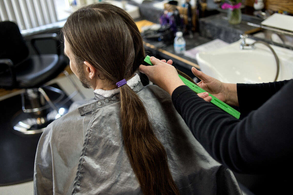 Hair stylist Diane King measures Lyle Saylor's hair before cutting it on Monday at Salon Elite Design Studio in Midland. His ponytails were 14 inches long. Saylor was donating his hair to Pantene Beautiful Lengths, a program which takes the hair and creates free, real-hair wigs for women with cancer. Saylor began donating his hair 10 years ago after his cousin was diagnosed with breast cancer.