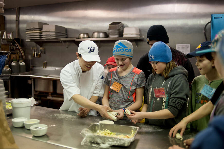 Plymouth Elementary School fifth-grader Allison Ferman, middle, and Madilyn Reneace are taught how to make egg rolls with their classmates by chef Yong Cheng at Golden Buffet in Midland on Tuesday. Photo: NEIL BLAKE | Nblake@mdn.net
