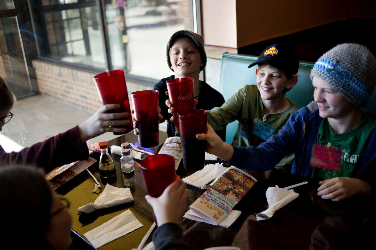 Plymouth Elementary School fifth-graders, from left, Mitch McMath, Stanton Millward and Danny Terburgh raise their glasses together while job shadowing Lily Sun, a waitress at Golden Buffet, on Tuesday.