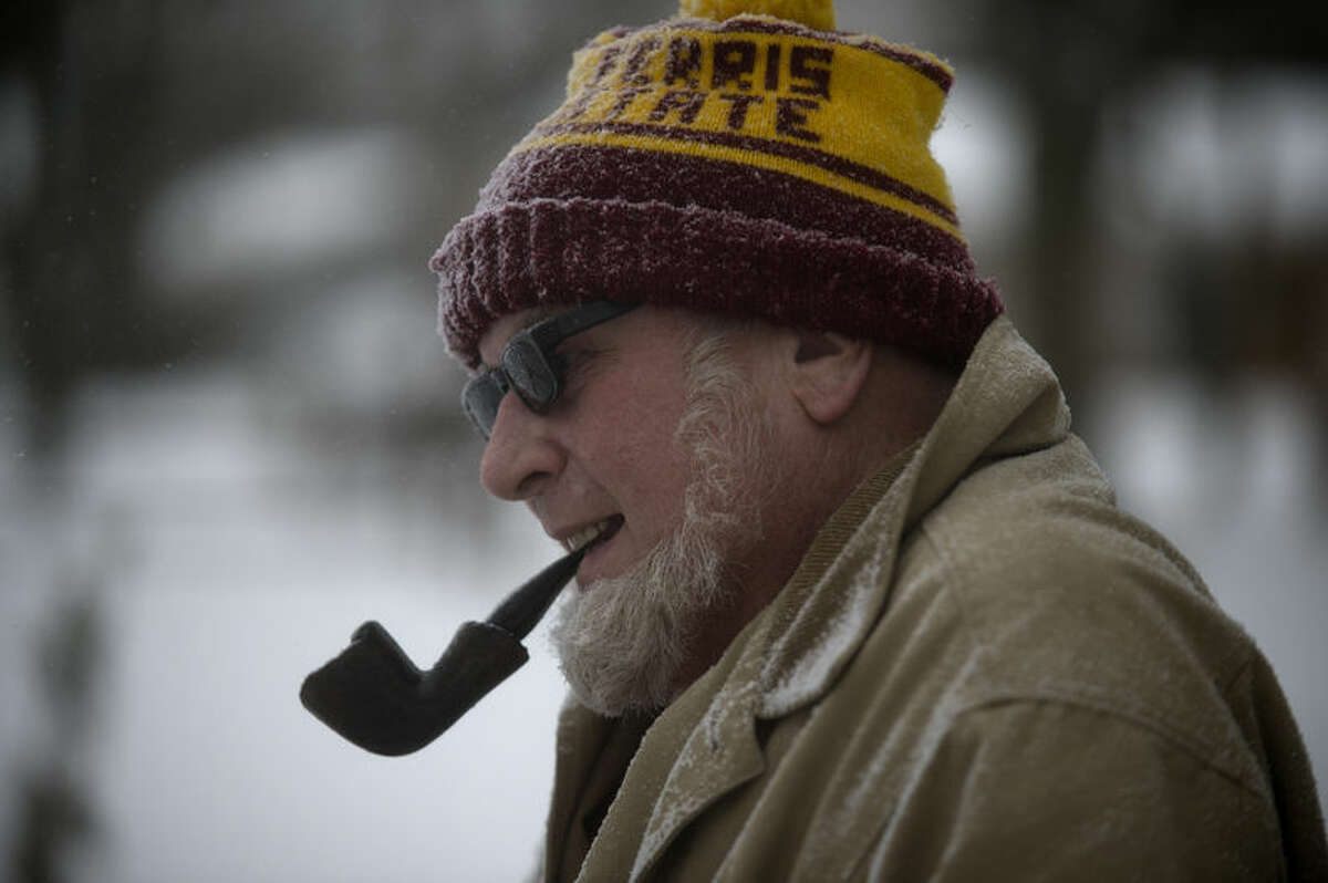 """Jerry Mlcek of Midland clears snow away from his neighbors' driveways March 3. Mlcek, who is retired, usually plows 12 driveways in his neighborhood as well as the sidewalks. """"I like to clean the sidewalks off before the kids get out of school so they have some place safe to walk,"""" Mlcek said."""
