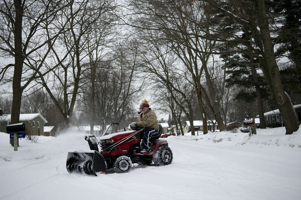 """Jerry Mlcek of Midland clears snow away from his neighbors' driveways March 3. """"I've been here for four years and I just like to help out whoever needs,"""" Mlcek said. Mlcek, who is retired, usually plows 12 driveways in his neighborhood, off of M-20, after it snows."""