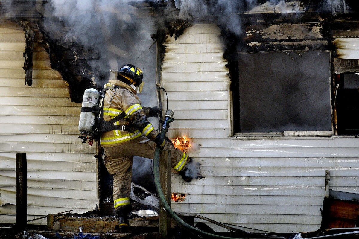 A firefighter kicks a hole in the siding near a door while working to put out a fire at a home on North Coleman Road between Oakwood Drive and Olson Road in Midland County on Sunday afternoon.