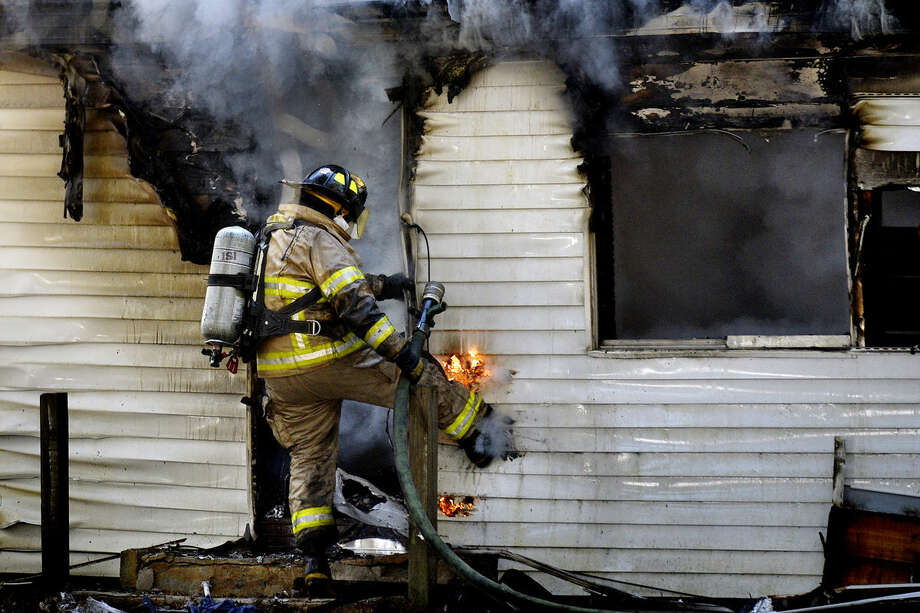 A firefighter kicks a hole in the siding near a door while working to put out a fire at a home on North Coleman Road between Oakwood Drive and Olson Road in Midland County on Sunday afternoon. Photo: NICK KING | Nking@mdn.net