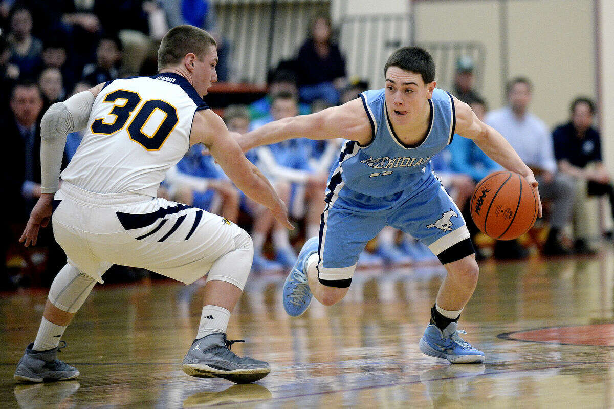 Meridian's Miles LeViere moves past Ithaca's Tyler Spitzley during the first quarter of Monday's Class C district basketball game at Merrill High School. Ithaca won 51-32.