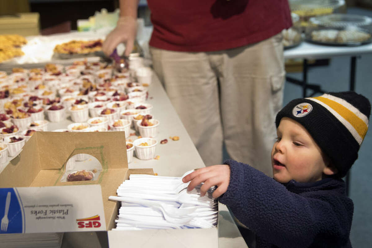 """James Anderson, 2, reaches for a fork at Ways to Wellness, featuring ABC pie from the Grand Traverse Pie Company for Pie Oh My Day in downtown Midland on Saturday. The event coincided with """"Pi Day,"""" named after the mathematical constant pi (π) whose first five digits are 3.1415. Fifteen downtown businesses hosted local bakeries and offered free pie samples."""