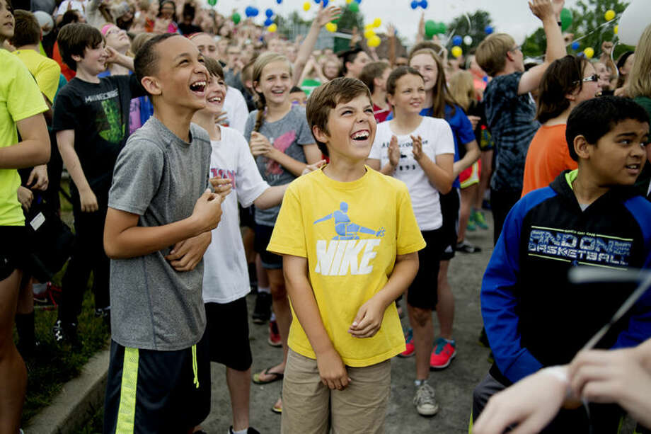 Northeast Middle School sixth-grader Brady Gardner, center right, laughs as he watches balloons float into the sky to send-off outgoing Principal Jeff Jaster on Friday. Photo: Neil Blake/Midland Daily News
