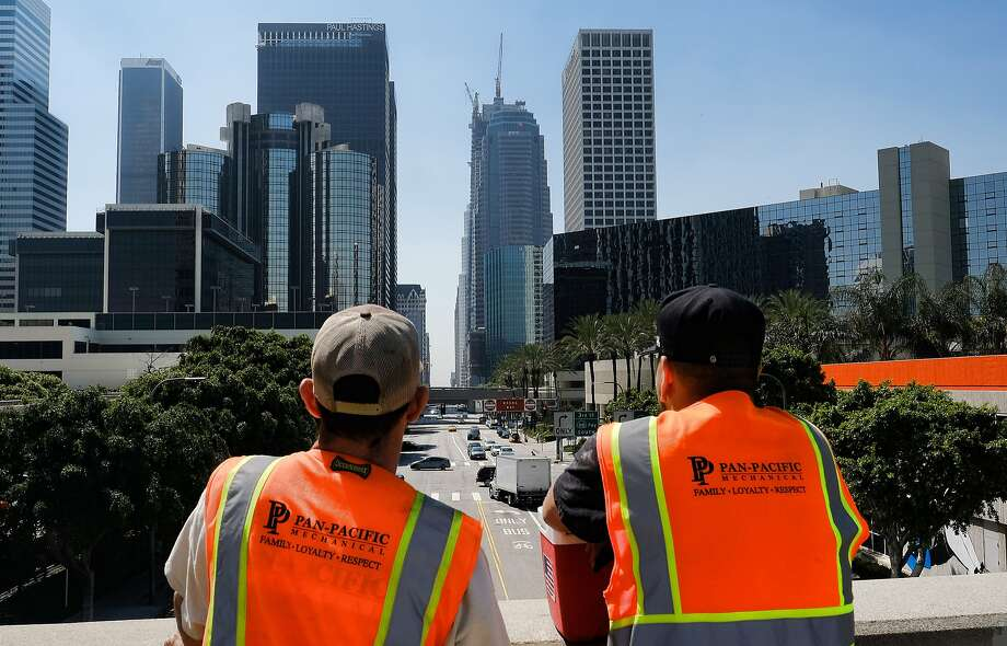 Maintenance workers look toward a skyscraper under construction where a worker fell to his death. The accident happened at one of the busiest times of day at one of the busiest intersections in Los Angeles. Photo: Richard Vogel, AP