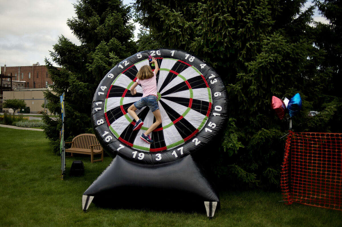 Brooklyn Moore, 10, jumps on a giant inflatable dart board to retrieve a dart while playing games with her sister, Madilyn, 12, during U.S. Rep. John Moolenaar's Picnic at the Tridge on Monday. Guests enjoyed a meal, games and carnival treats.