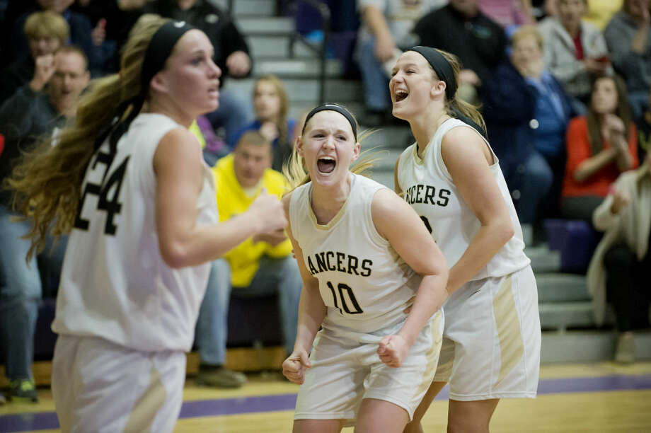 Bullock Creek's Hannah Heldt, center, and Madison Hill celebrate Hill's 3-pointer to tie the game against Freeland as Ellie Juengel looks to the sideline at Caro High School on Tuesday. Photo: Neil Blake/Midland Daily News