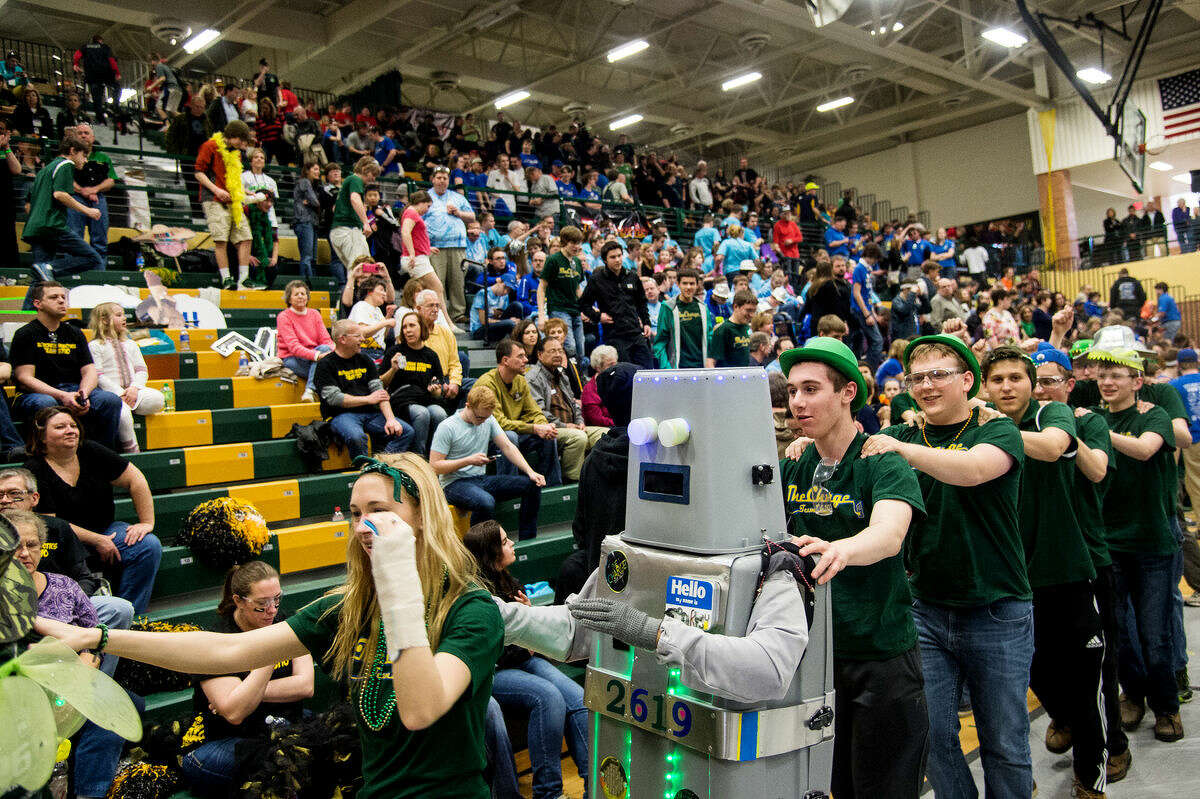 The Dow High School student section celebrates with a conga line featuring their robot mascot at the Great Lakes Bay Region Robotics District Competition at H.H. Dow High School on Saturday afternoon in Midland.