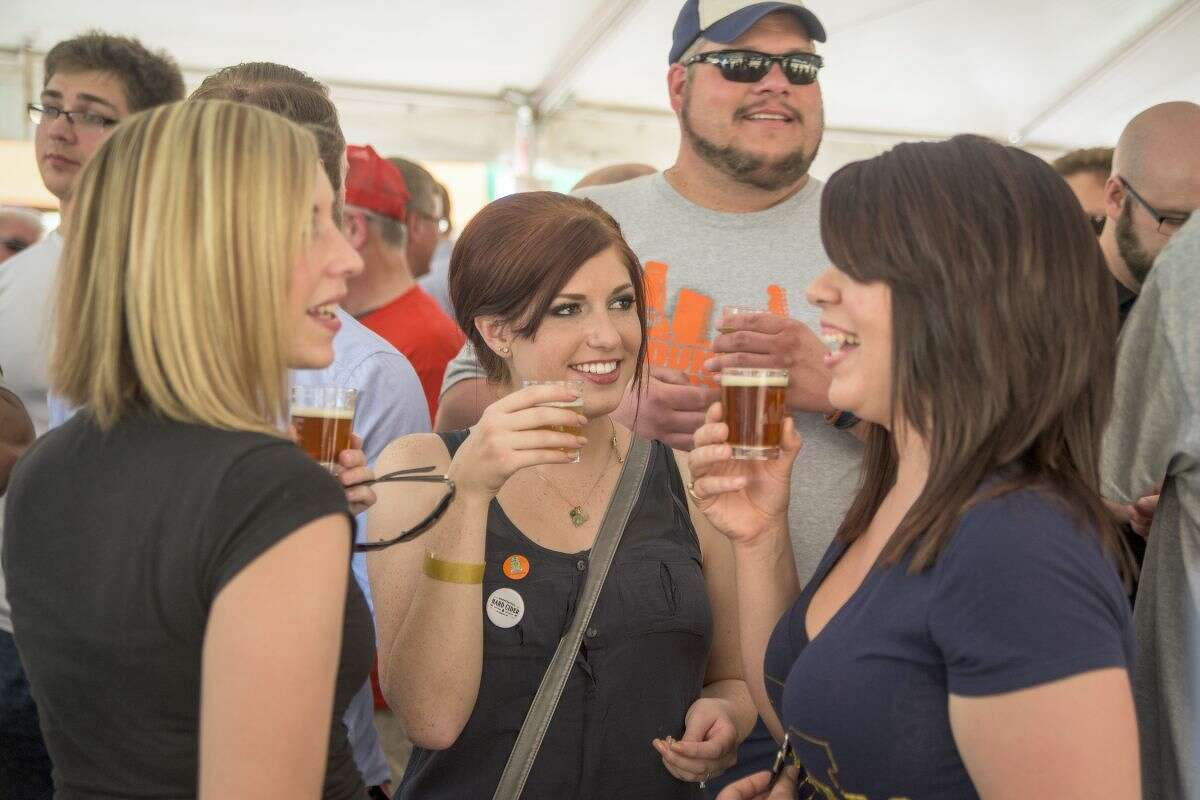 Alyssa Peterson of South Bend, Julia Yowler of Midland, and Ashley Trombley of Midland chat and sample beers from the Right Brain Brewery in Traverse City during the Tapped craft beer festival in downtown Midland on Saturday.