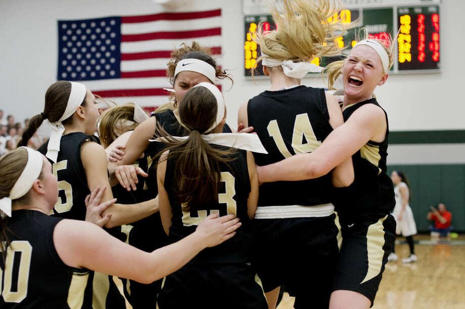 Bullock Creek's Hannah Heldt, right, hugs her sister, Haley, after Creek's win over John Glenn at Pinconning High School on Wednesday. Photo: Neil Blake/Midland Daily News
