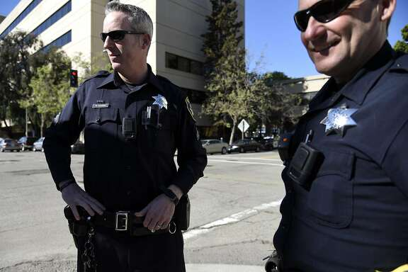 Officers Mike Cooper, left, and officer John Hargraves talk with fellow officers in front of the Oakland Police Department Headquarters in Oakland, CA Thursday, March 17, 2016.