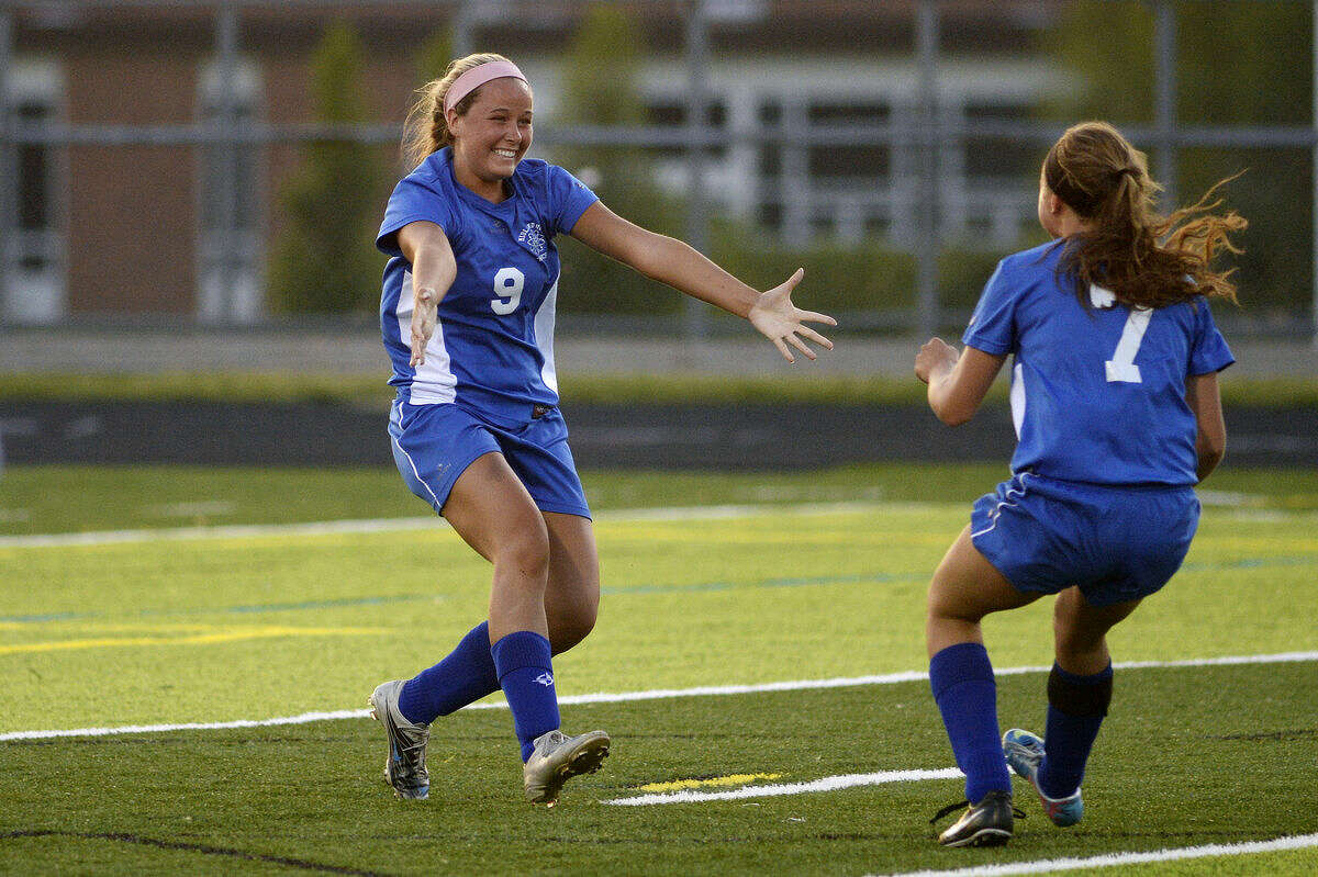 Midland's Lexi Traver, left, celebrates her goal with teammate Megan Arlt during the second half on Wednesday at Forrest Hills Central High School in Grand Rapids. The Chemics won 1-0.