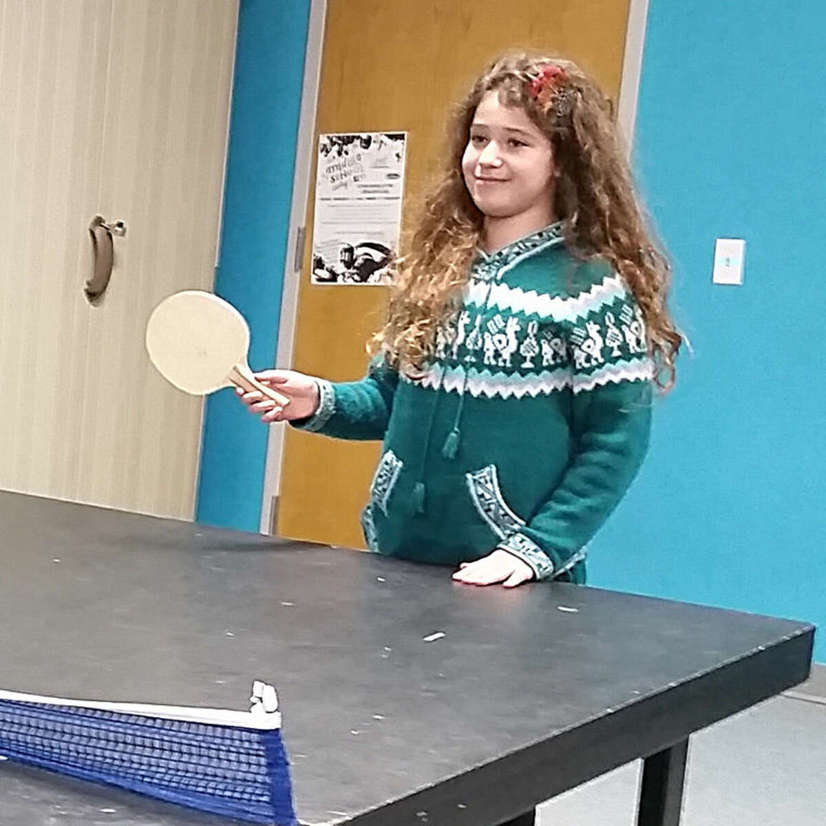 Anne Ginzburg, a sixth-grader, enjoys a game of ping-pong at The ROCK Underground.