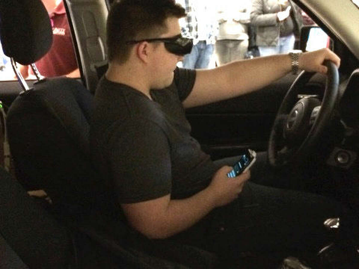 A local student texts while driving in the Arrive Alive simulator.