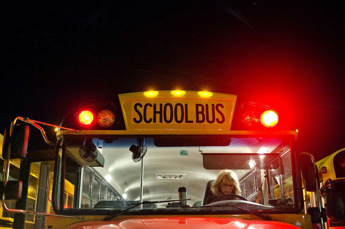 Midland Public Schools bus driver Dana Hahn runs through her checklist to prepare for her morning bus route in the bus parking lot.