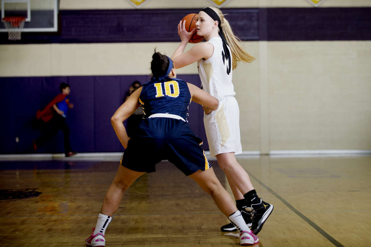 Bullock Creek's Haley Heldt looks to pass guarded by Goodrich's Alexis Sullivan at Caro High School on Thursday.