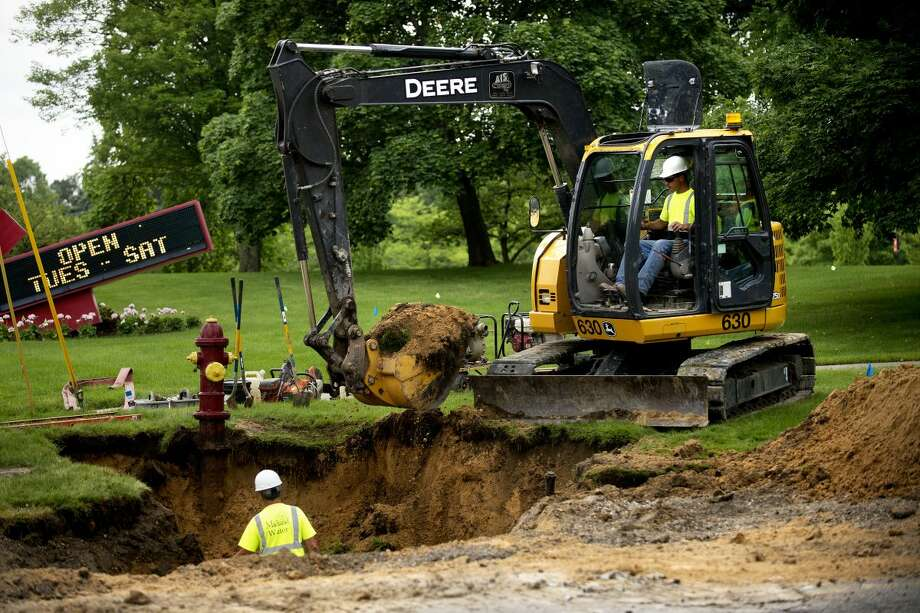Construction crews dig around a fire hydrant at the intersection of St. Andrews Road and Eastman Avenue on Wednesday. Eastman Avenue construction is expected to be completed in November and will repair the road to just north of Saginaw Road. Photo: Neil Blake   Nblake@mdn.net