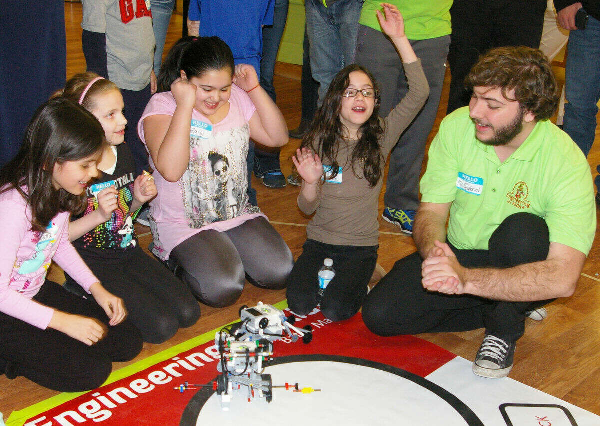 A group of youths cheer as they watched their robots compete at the Engineering for Kids workshop.
