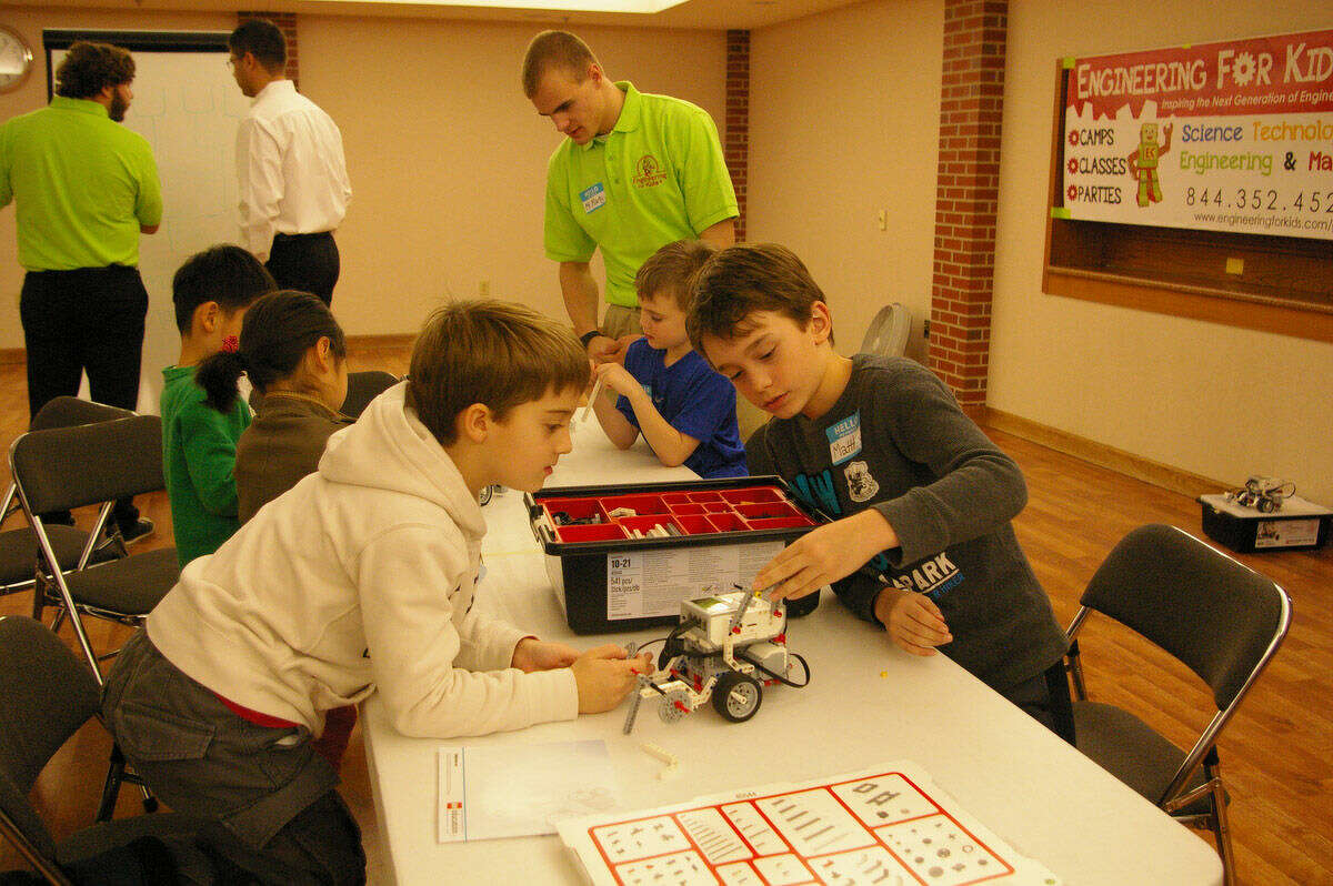 The youths worked in teams to finish a robot at the Engineering for Kids workshop at the Midland Community Center.