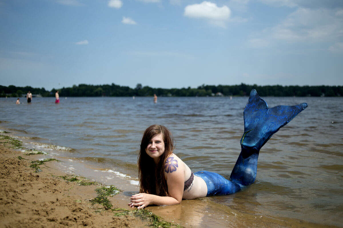 """Jenna Eschenburg of Midland smiles for a portrait at Sanford Lake Park. Eschenburg started hosting parties as a mermaid the past December and when she was younger told people she wanted to be a mermaid when she grew up. """"I've been duct-taping my legs together since I was 3,"""" she said. """"So it's easy for me to swim with my tail."""""""