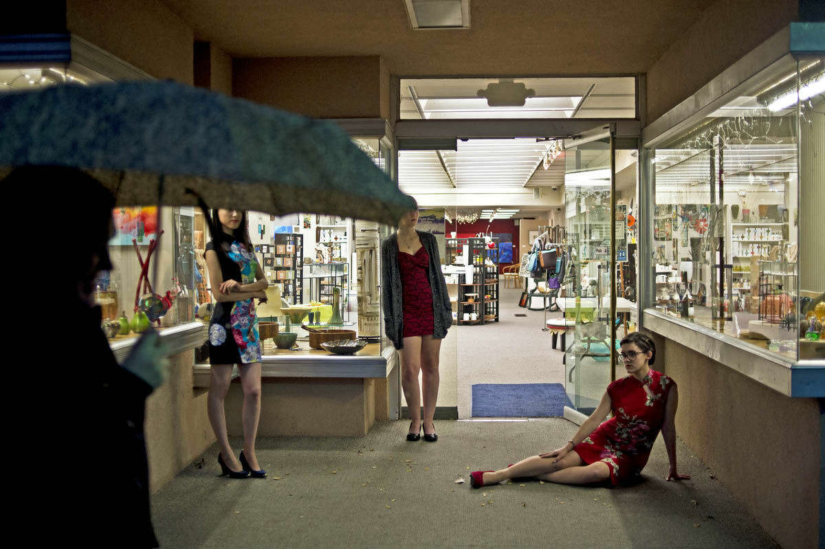 Bystanders pass by and watch as Northwood students Yvonie Wang, 23, Kristy Godley, 18, and Emily Williams, 18, pose in the doorway of Northwood University Gallery during Mannequin Night.
