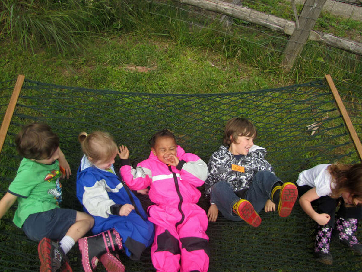 Children play on a hammock at the Nature Preschool. The Nature Preschool at Chippewa Nature Center is expanding for the 2015-16 school year in an effort to meet demand for the program.