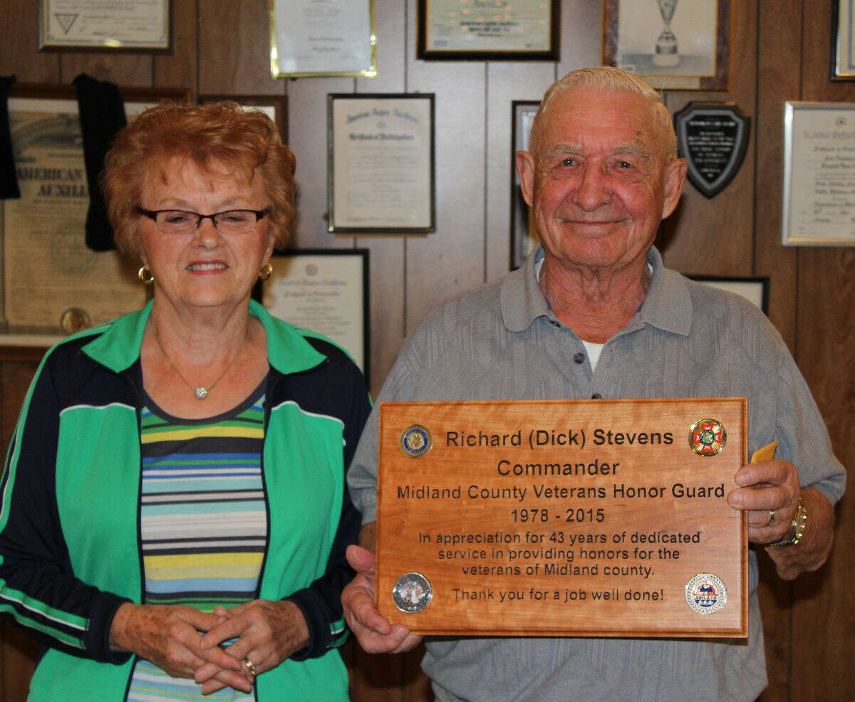 Dick Stevens, accompanied by his wife, Kathleen, displays the plaque that was presented to him at last week's annual Midland County Veterans Honor Guard dinner program