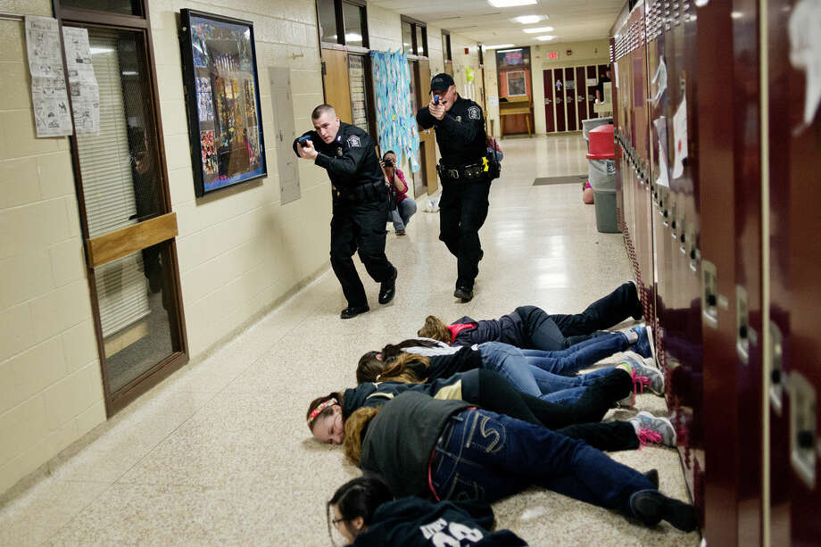 Beaverton Police officers Nathan Day, left, Richard Ward, right, move down the hallway toward an armed intruder during a simulation at Beaverton Elementary School. The training was conducted by security expert Thomas Royal. Photo: NICK KING | Nking@mdn.net