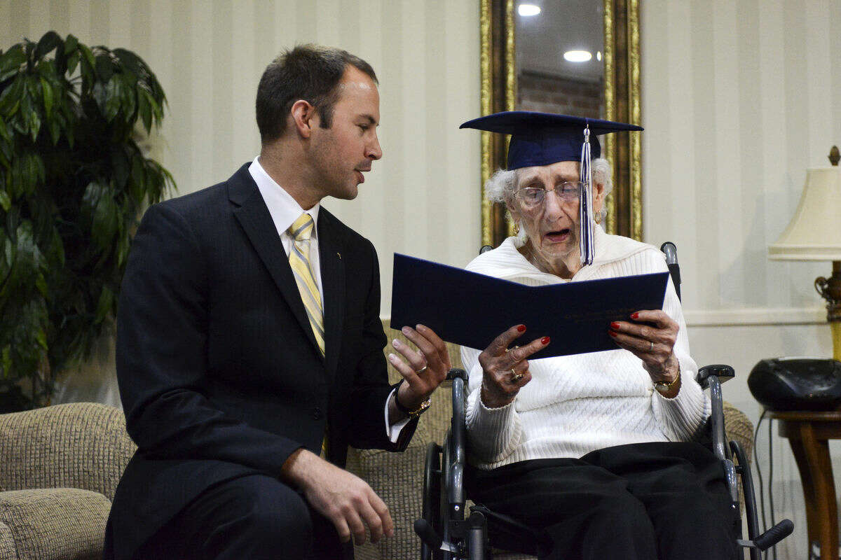 Catholic Central High School Principal Greg Deja, left, presents 97-year-old Margaret Thome Bekema with her honorary diploma at Stonebridge Manor on Thursday, Oct. 29, 2015 in Grand Rapids, Mich.. Bekema began her education at Catholic Central in 1932 but sacrificed completing her degree at that time to take care of her mother who had cancer and her younger siblings.