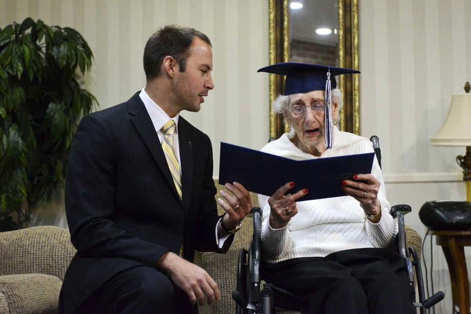 Catholic Central High School Principal Greg Deja, left, presents 97-year-old Margaret Thome Bekema with her honorary diploma at Stonebridge Manor on Thursday, Oct. 29, 2015 in Grand Rapids, Mich.. Bekema began her education at Catholic Central in 1932 but sacrificed completing her degree at that time to take care of her mother who had cancer and her younger siblings. Photo: Emily Rose Bennett / The Grand Rapids Press Via AP