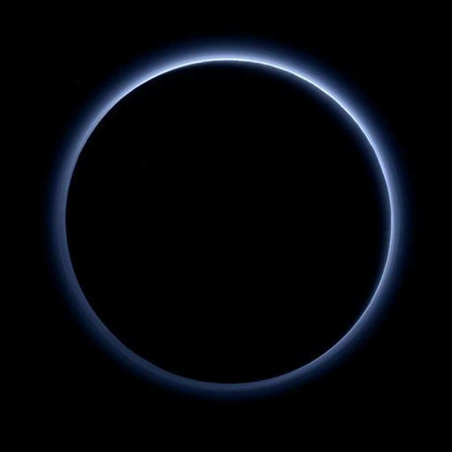 This image released by NASA on Thursday, Oct. 8, 2015, shows the blue color of Pluto's haze layer in this picture taken by the New Horizons spacecraft's Ralph/Multispectral Visible Imaging Camera (MVIC). The high-altitude haze is thought to be similar in nature to that seen at Saturn's moon Titan. This image was generated by software that combines information from blue, red and near-infrared images to replicate the color a human eye would perceive as closely as possible. (NASA/JHUAPL/SwRI via AP Photo: HOGP