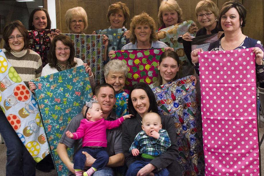 Lori Frollo, far right, family and friends pose after knitting quilts for Neonatal Intensive Care Unit at Covenant Hospital in the basement of the Mercantile Bank in Merrill. Frollo had this idea after her twin grandchildren, Claire and Cole, were in the Neonatal Intensive Care Unit for seven weeks and wanted to donate some quilts to the facility. Photo: AP Photo | The Saginaw News, Andrew Whitaker