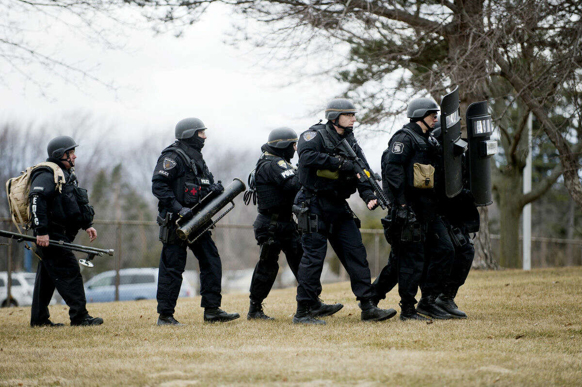 Saginaw Emergency Services Team members walk conduct a training exercise in conjunction with the Midland S.W.A.T. team at Parkdale Elementary in Midland on Thursday. The routine training lasted from 2 p.m. to 8 p.m. and was a barricaded gunman scenario.