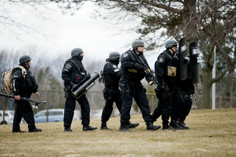 Saginaw Emergency Services Team members walk conduct a training exercise in conjunction with the Midland S.W.A.T. team at Parkdale Elementary in Midland on Thursday. The routine training lasted from 2 p.m. to 8 p.m. and was a barricaded gunman scenario. Photo: Neil Blake/Midland Daily News
