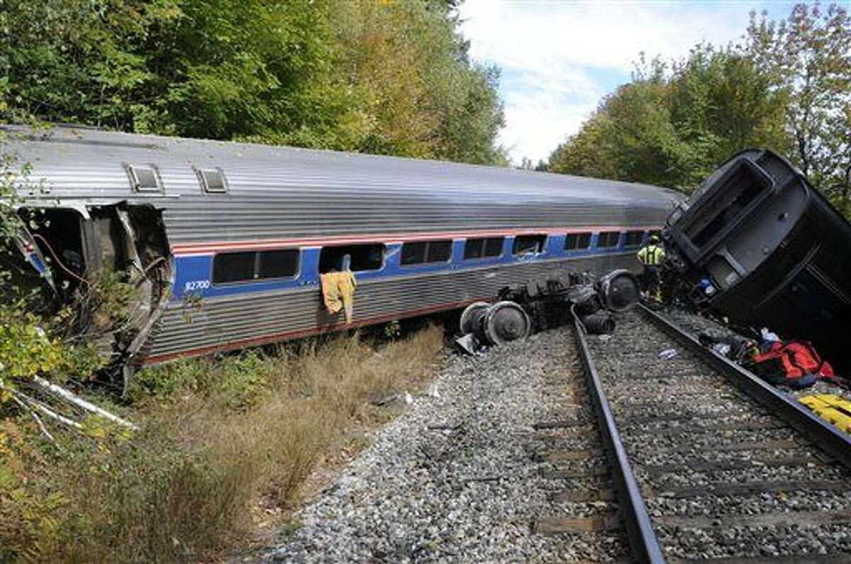 A first responder, right, examines railroad passenger cars at the scene of an Amtrak passenger train derailment Monday, Oct. 5, 2015, in Northfield, Vt. The train, the Vermonter, was headed from Vermont to Washington, D.C., when it apparently struck rocks that were on the tracks. No life-threatening injuries were reported. (Stefan Hard/Barre-Montpelier Times Argus via AP) MANDATORY CREDIT