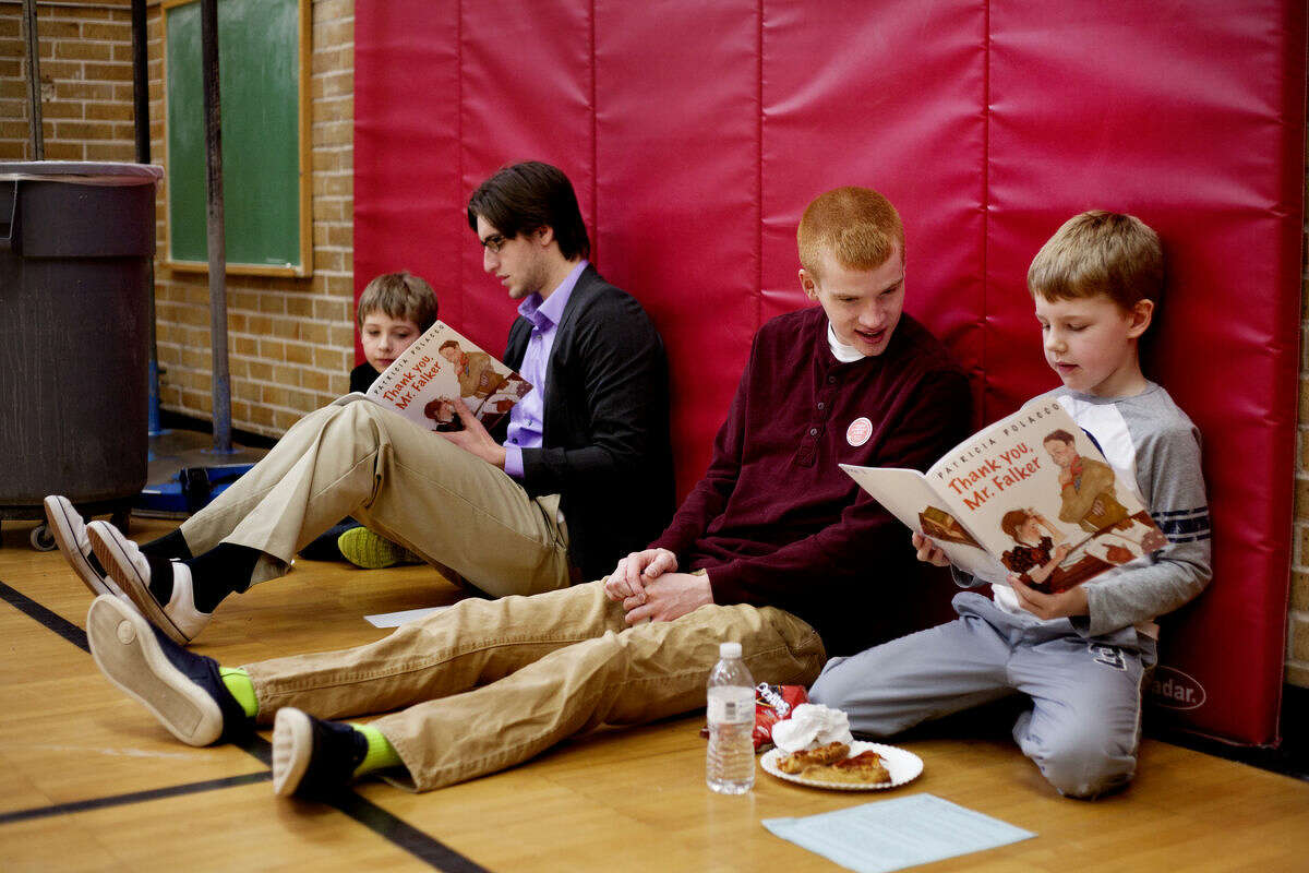 Tyler Makins, third from left, a sophomore at Northwood University, looks on as second-grader Drew Vanderwaal, far right, reads while Sam Martus, a senior at Northwood, reads to second-grader James Dodd at Carpenter Street School on Wednesday. The event was for March is Reading Month and was sponsored by United Way and its Young Leaders United and Student United Way. Volunteers were paired with students to read during a free pizza lunch.