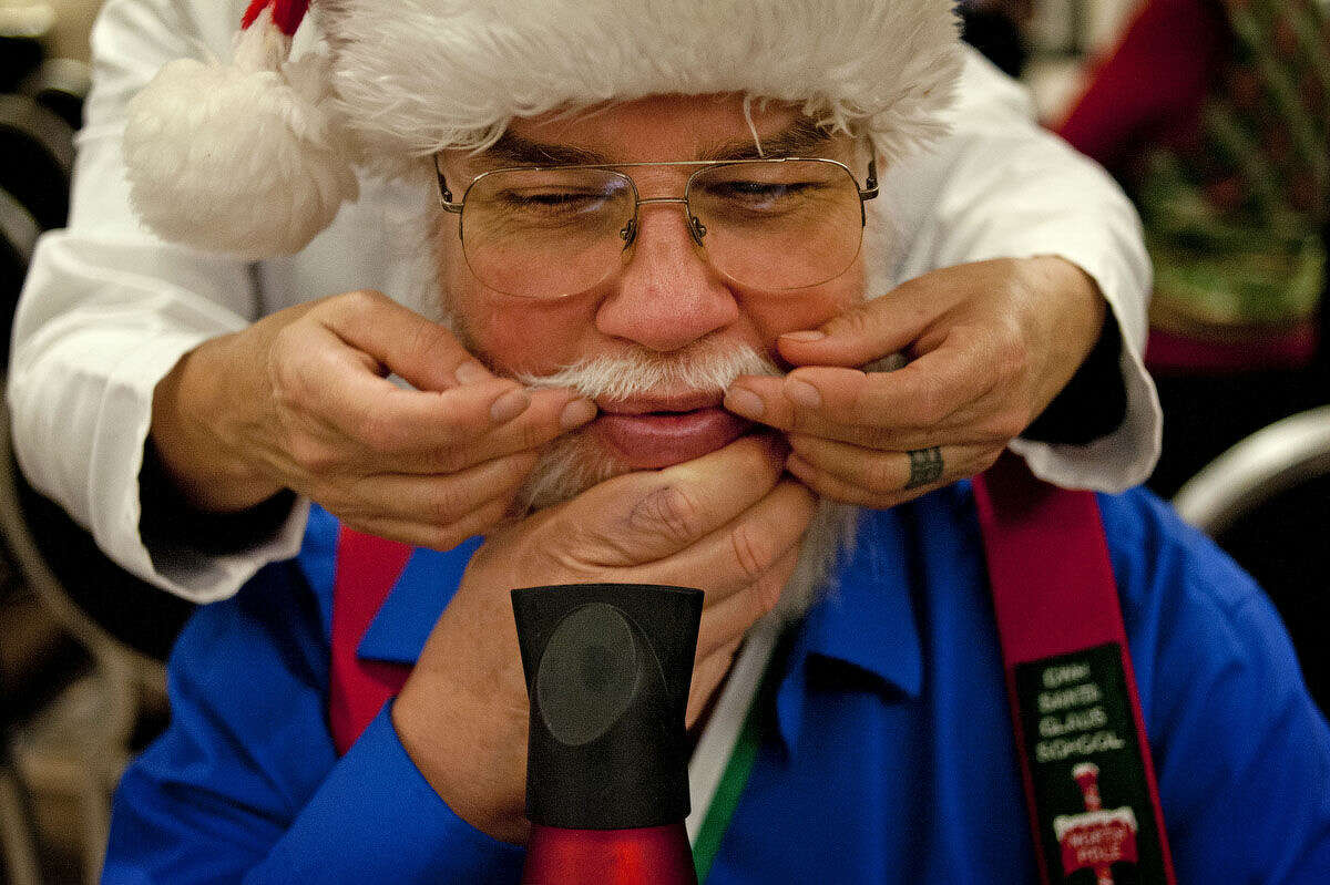 Sue Myers of Midland helps Dan Babock of Wheaton, Ill. curl the edges of his mustache at the H Hotel on the first day of the Charles W. Howard Santa Claus School.