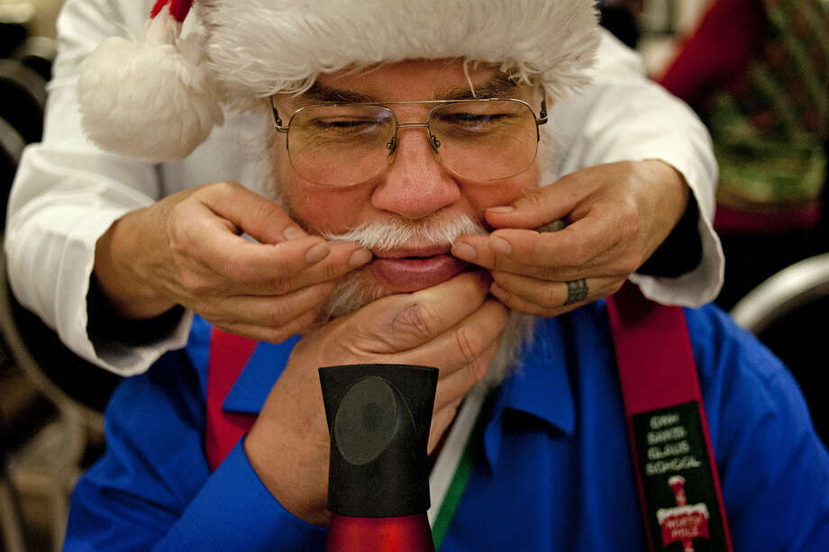 Sue Myers of Midland helps Dan Babock of Wheaton, Ill. curl the edges of his mustache at the H Hotel on the first day of the Charles W. Howard Santa Claus School. Photo: Brittney Lohmiller | Midland Daily News