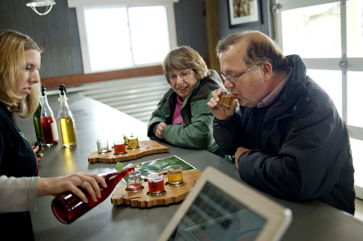 Ron Lacher, right, of Midland, and his wife, Jane, center, sample different hard cider poured by employee Erika Kopulos at Eastman's Forgotten Ciders at 1058 West Midland-Gratiot County Line Road in Wheeler. The new business offers homemade hard ciders for sale and for tasting.