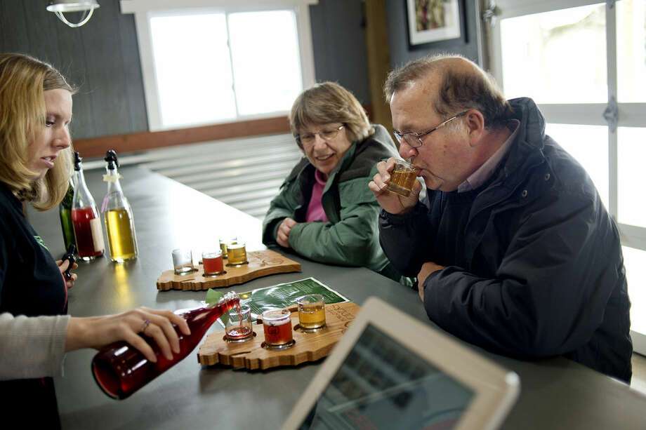 Ron Lacher, right, of Midland, and his wife, Jane, center, sample different hard cider poured by employee Erika Kopulos at Eastman's Forgotten Ciders at 1058 West Midland-Gratiot County Line Road in Wheeler. The new business offers homemade hard ciders for sale and for tasting. Photo: NICK KING | Nking@mdn.net