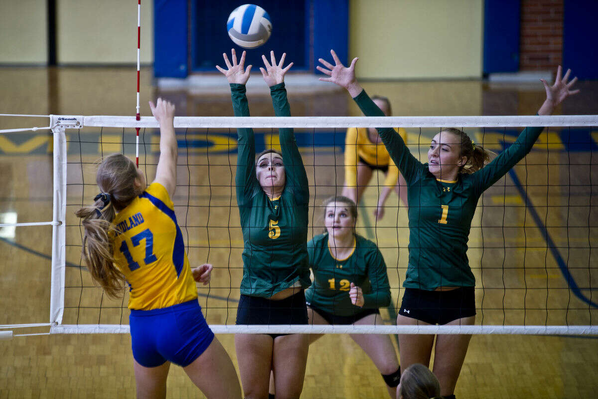 Midland's Grace Rekeweg spikes the ball over the net and towards Dow's Sofia Lobo, left, and Ariana Hempfling, right, during the first set on Tuesday at Midland High School. The Chargers defeated the Chemics in a close, five-set series.