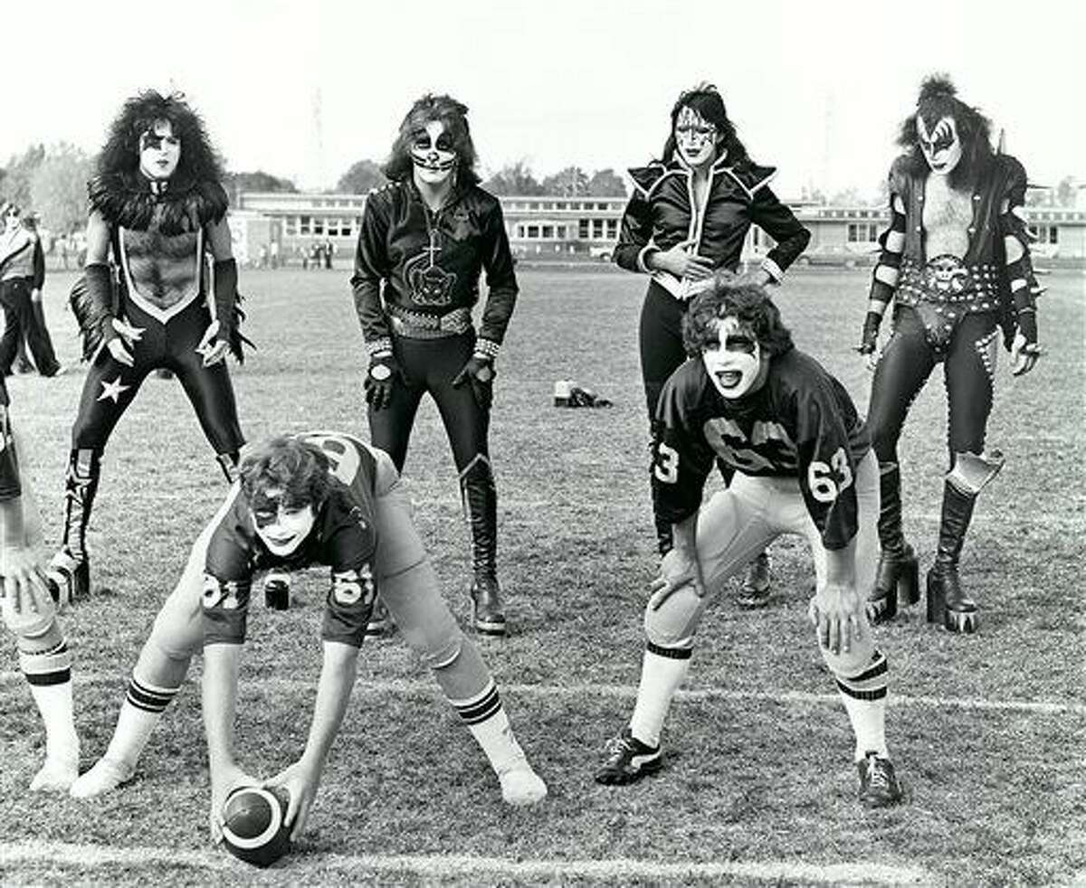 In this Oct. 9, 1975 file photo, members of the rock band KISS, from top left: Paul Stanley, Peter Criss, Ace Frehley and Gene Simmons, line up behind two members of the Cadillac High School Vikings football team, wearing KISS facepaint, in Cadillac.