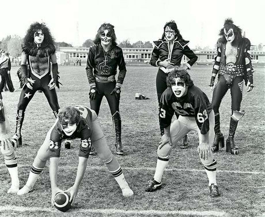 In this Oct. 9, 1975 file photo, members of the rock band KISS, from top left: Paul Stanley, Peter Criss, Ace Frehley and Gene Simmons, line up behind two members of the Cadillac High School Vikings football team, wearing KISS facepaint, in Cadillac. Photo: Mike McCarty | Cadillac News Via AP, File