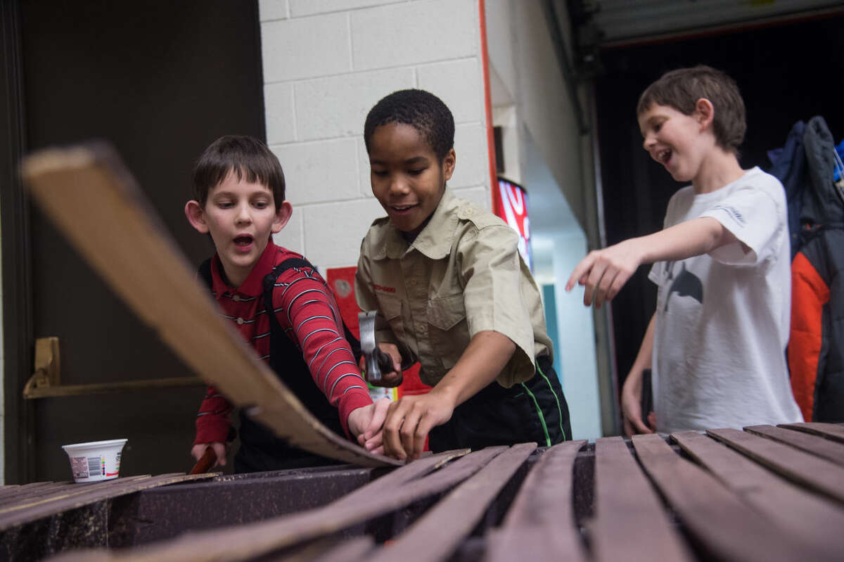 ZACK WITTMAN | For the Daily News From left: Boy Scouts from Troop 778 Stanton Millward, Luke Pierce and Lawrence Millward, all 11-years-old, help build the set for the upcoming play, Sugar Bean Sisters, Tuesday evening backstage at the Midland Center for the Arts. The set is for the touring Sugar Bean Sisters production, part of the 2015 AACTFest.