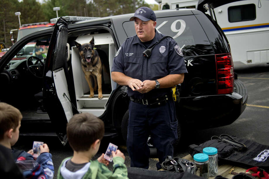 Midland Police Officer Greg Tait talks with brothers Corbin, 5, center, and Bridger Ouderkirk, 6, about Brody the bomb dog, background, during the Mills Township Fire Department's annual fire safety open house on Monday. Photo: Nick King | Midland Daily News